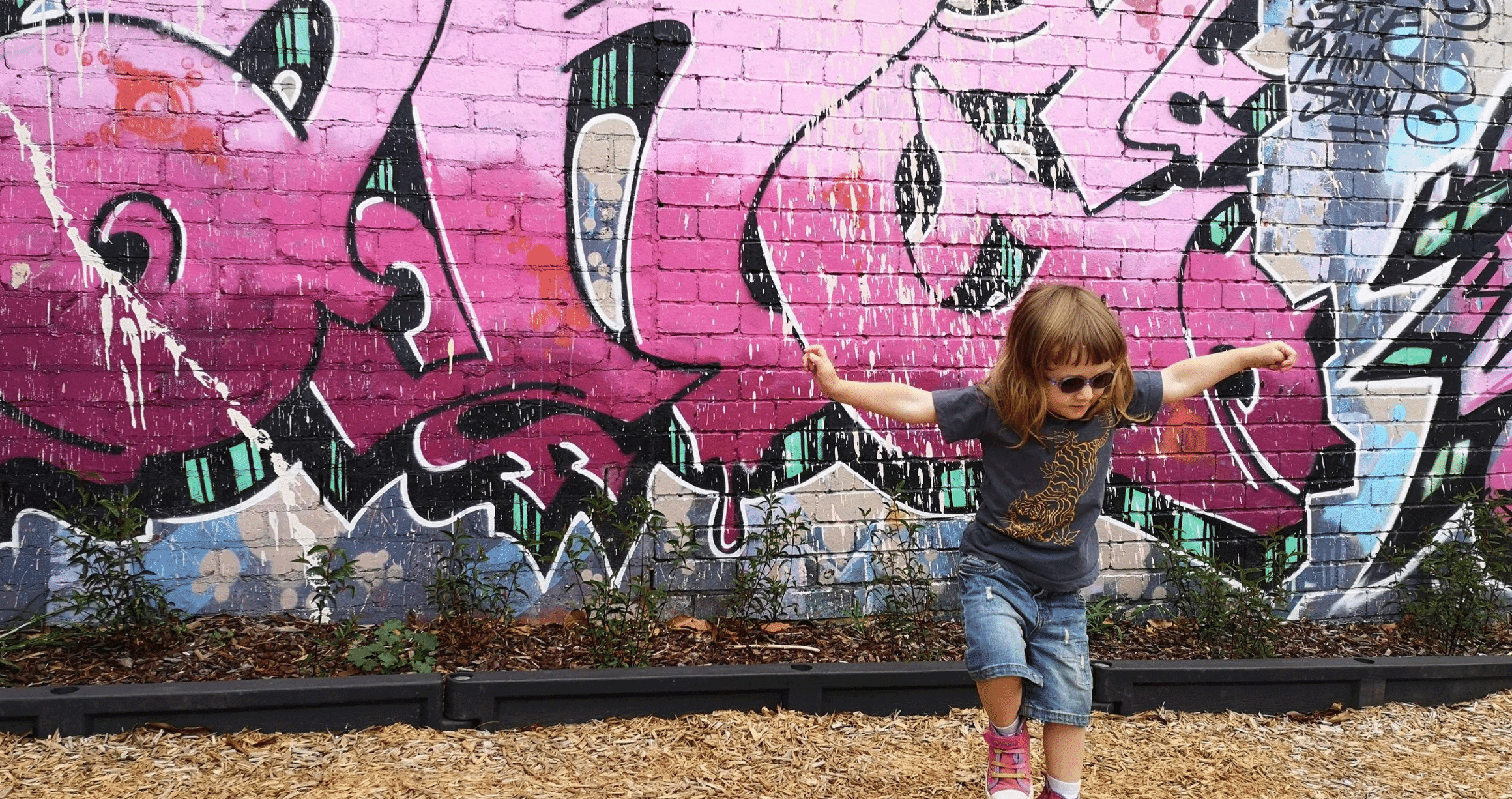 Young girl wearing glasses, playing happily in front of brick graffiti wall, very colourful