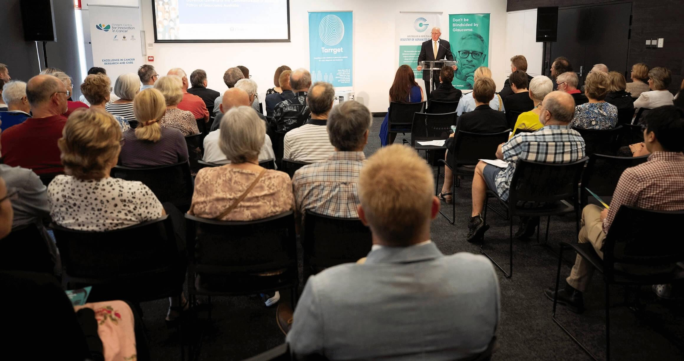image from rear perspective of audience in a conference room listening to the Governor General of Australia explain the importance of glaucoma awareness