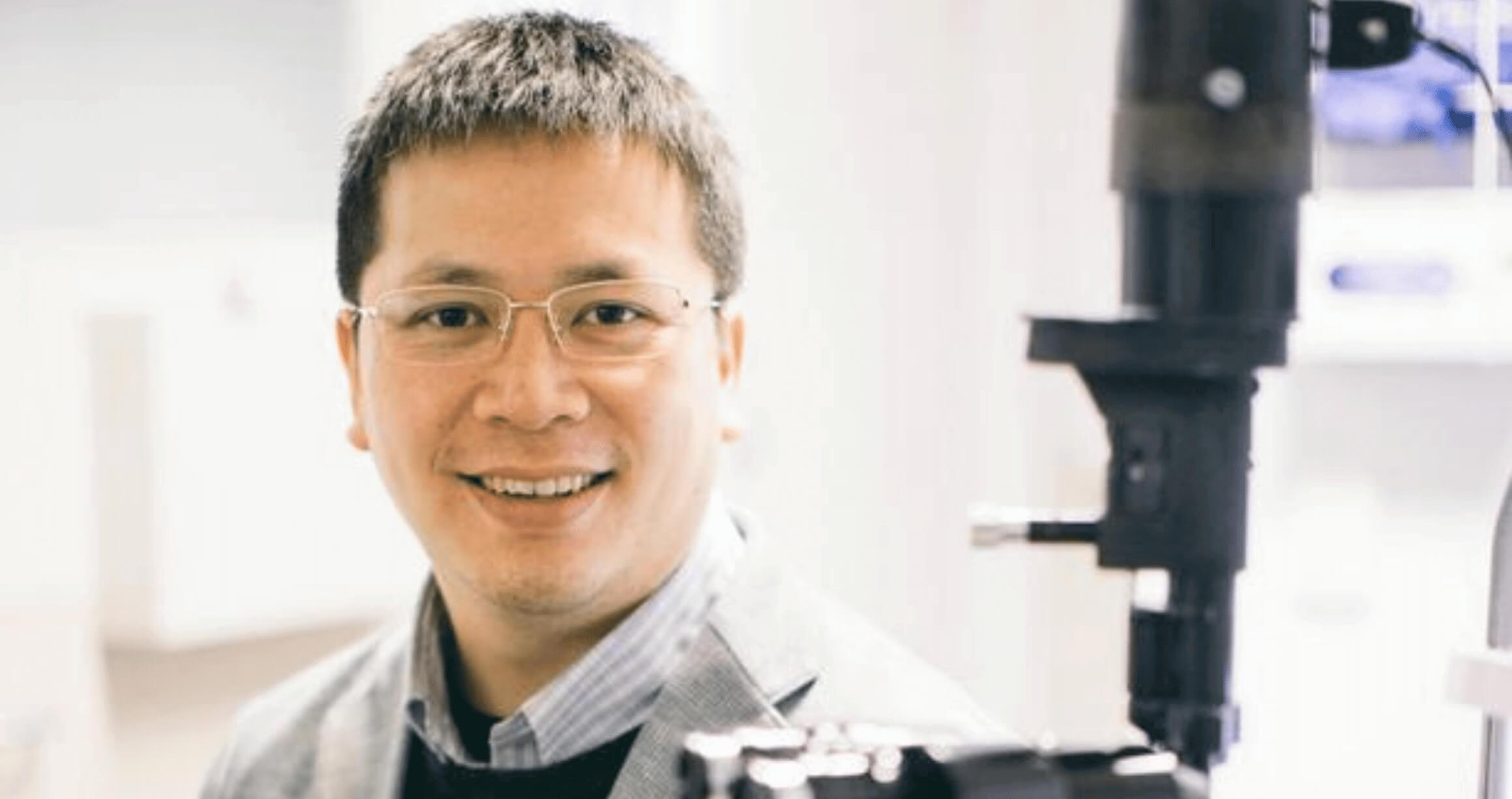 image of male doctor sitting in lab wearing coat and glasses with large microscope