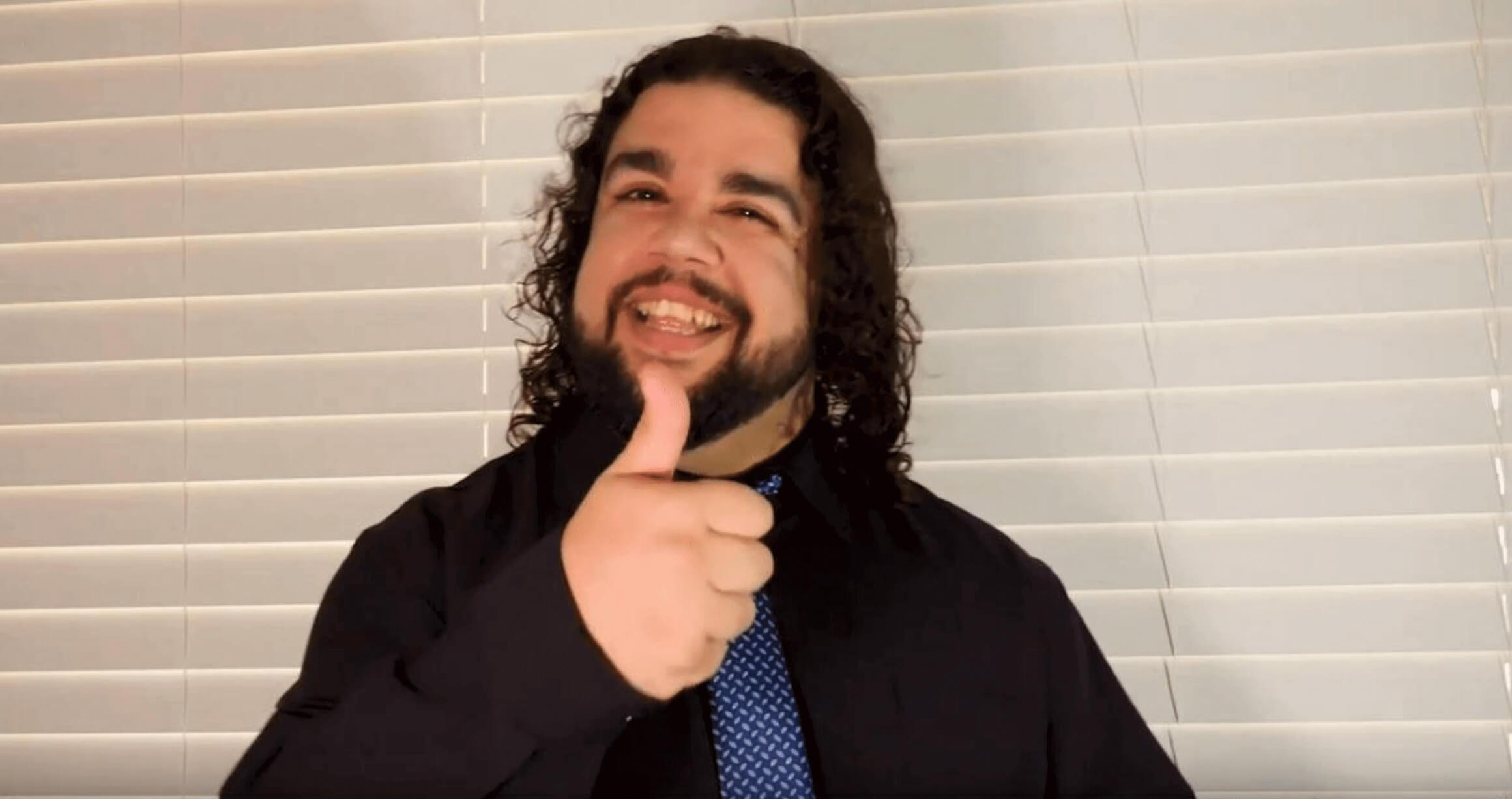 image of young man with shoulder length wavy black hair, smiling at camera and giving thumbs up