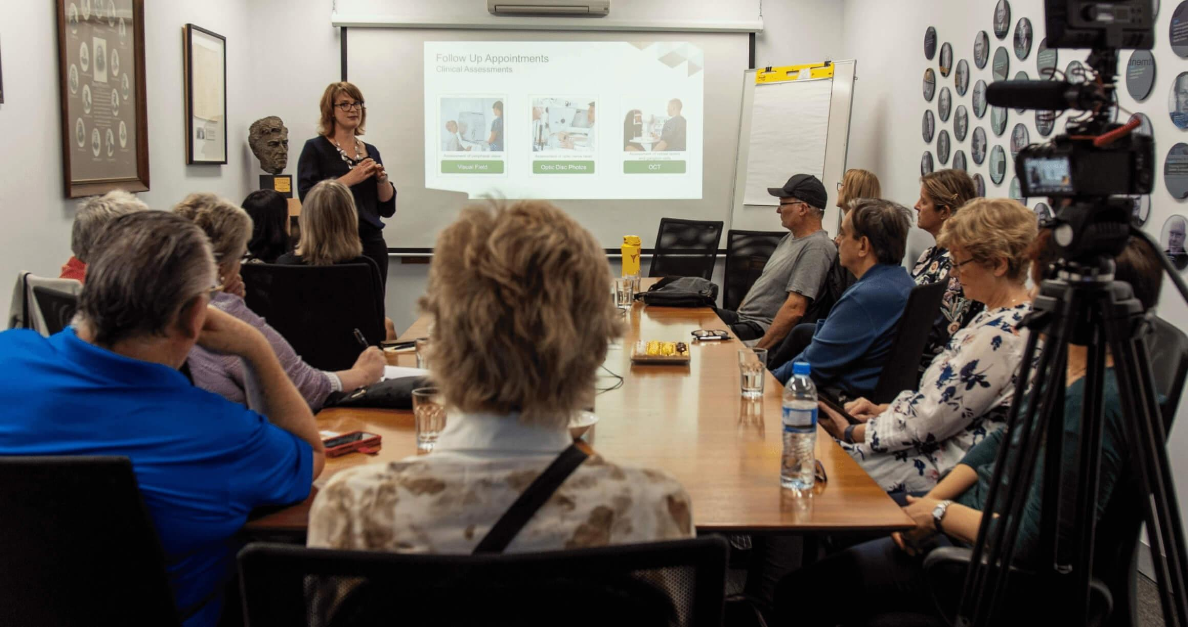 image of boardroom table with several people sitting around watching and listening to a woman give a presentation on a projector screen