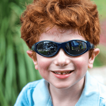 Young red head boy in light blue polo wearing sunglasses