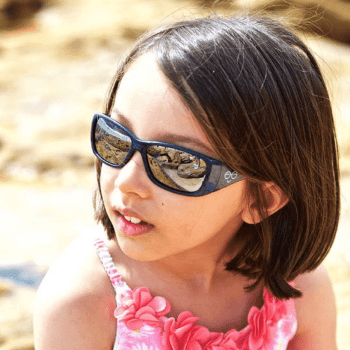 Young dark haired girl at beach wearing sunglasses