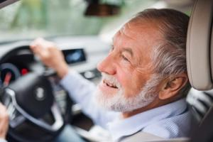 An older man with a grey beard sitting behind the wheel of a car