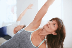 Middle aged woman stretching her arm over her head during a yoga class