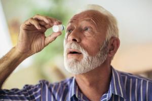 Older man administering eye drops